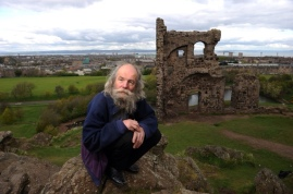 Jake Williams, a hermit who lives in the Cairngorms, crouches on Arthur's Seat, Edinburgh